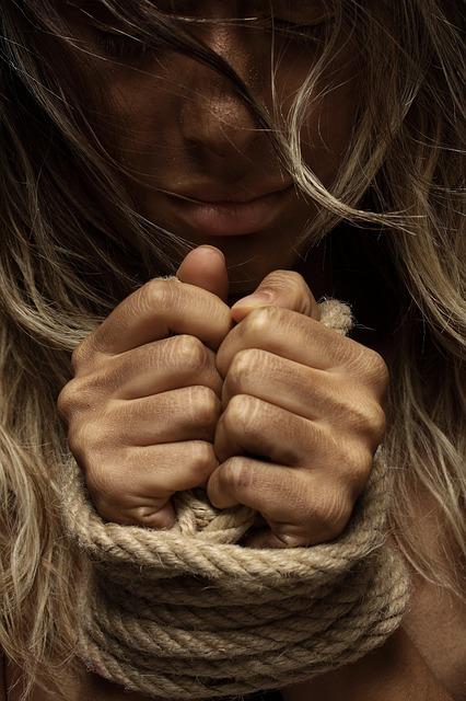 Frau an Handgelenken gefesselt